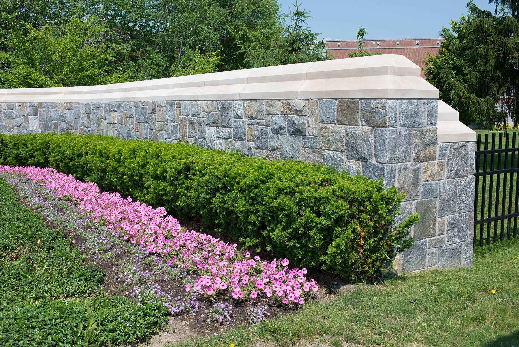 stone wall with flowers and bushes