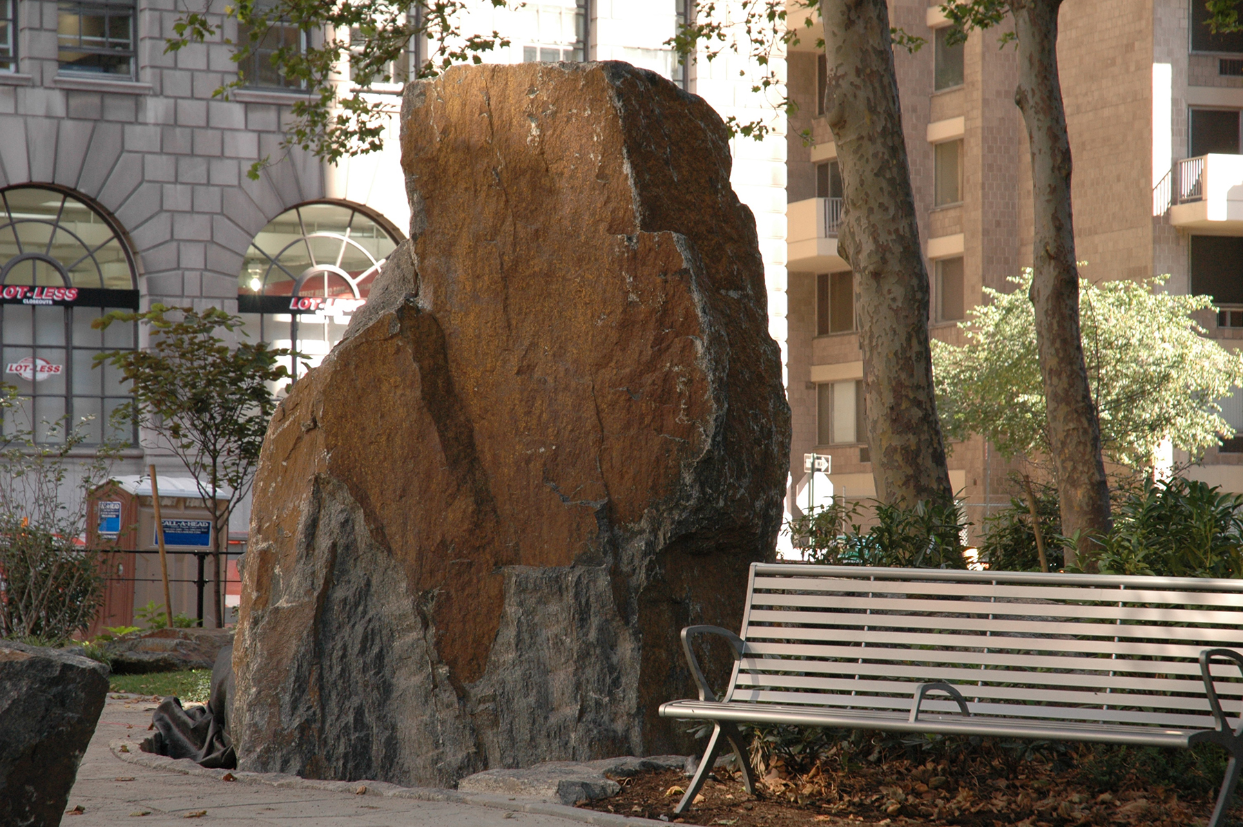 Large stone in park near bench