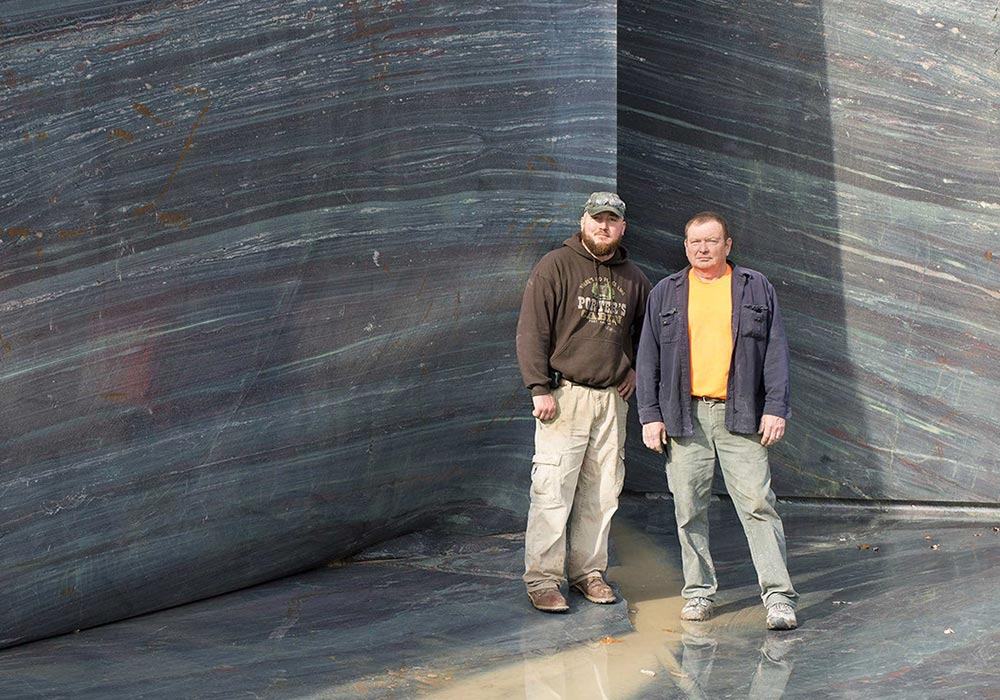 two quarry workers in front of granite slab