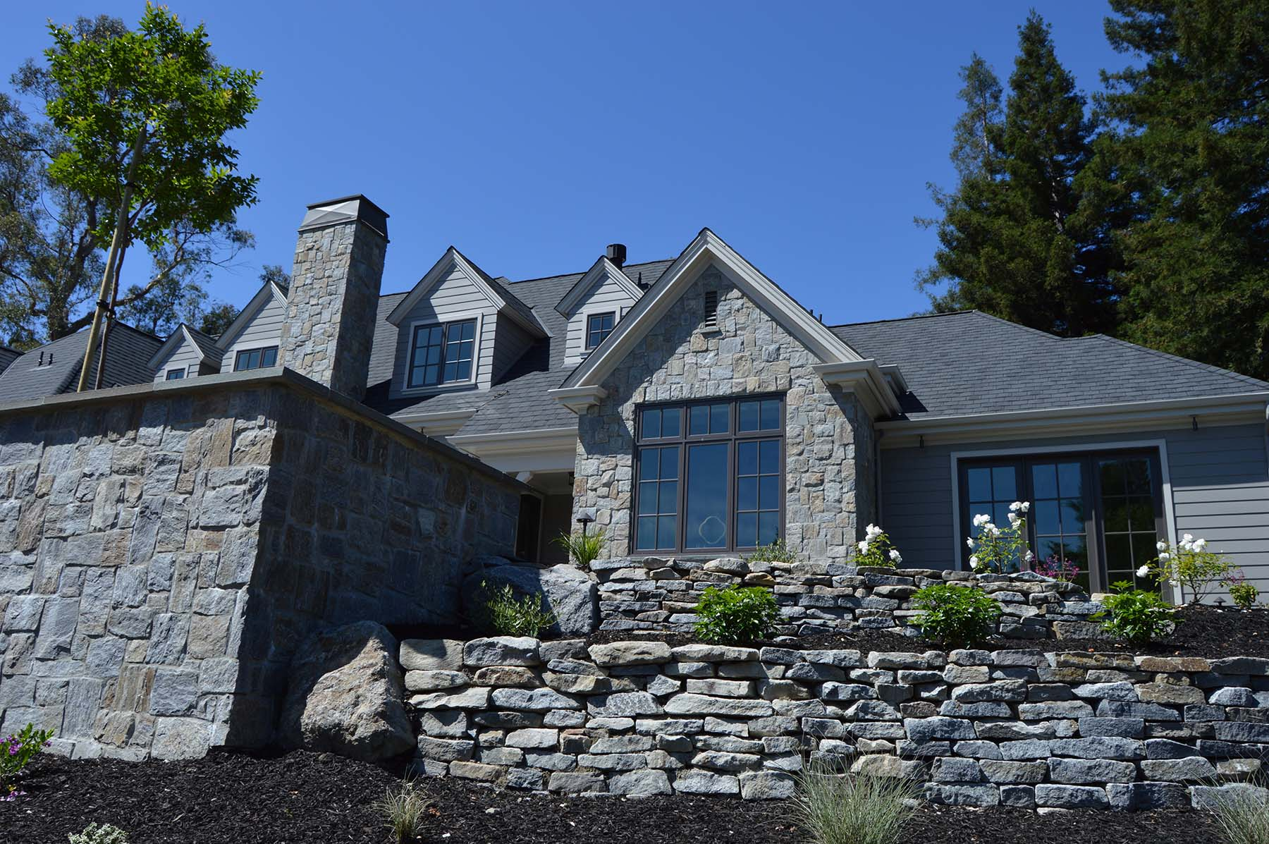 natural stone wall retaining wall and thin stone exterior at Toledo Court