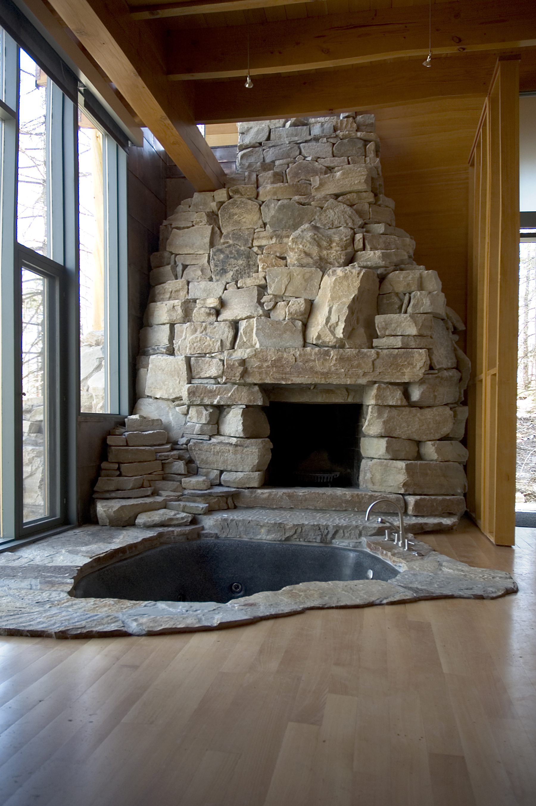 stone hot tub next to fireplace