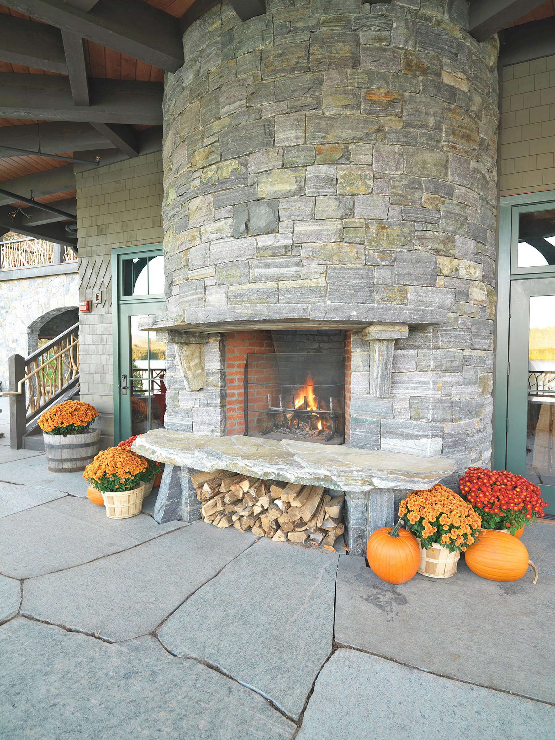 stone fireplace with pumpkins and flowers