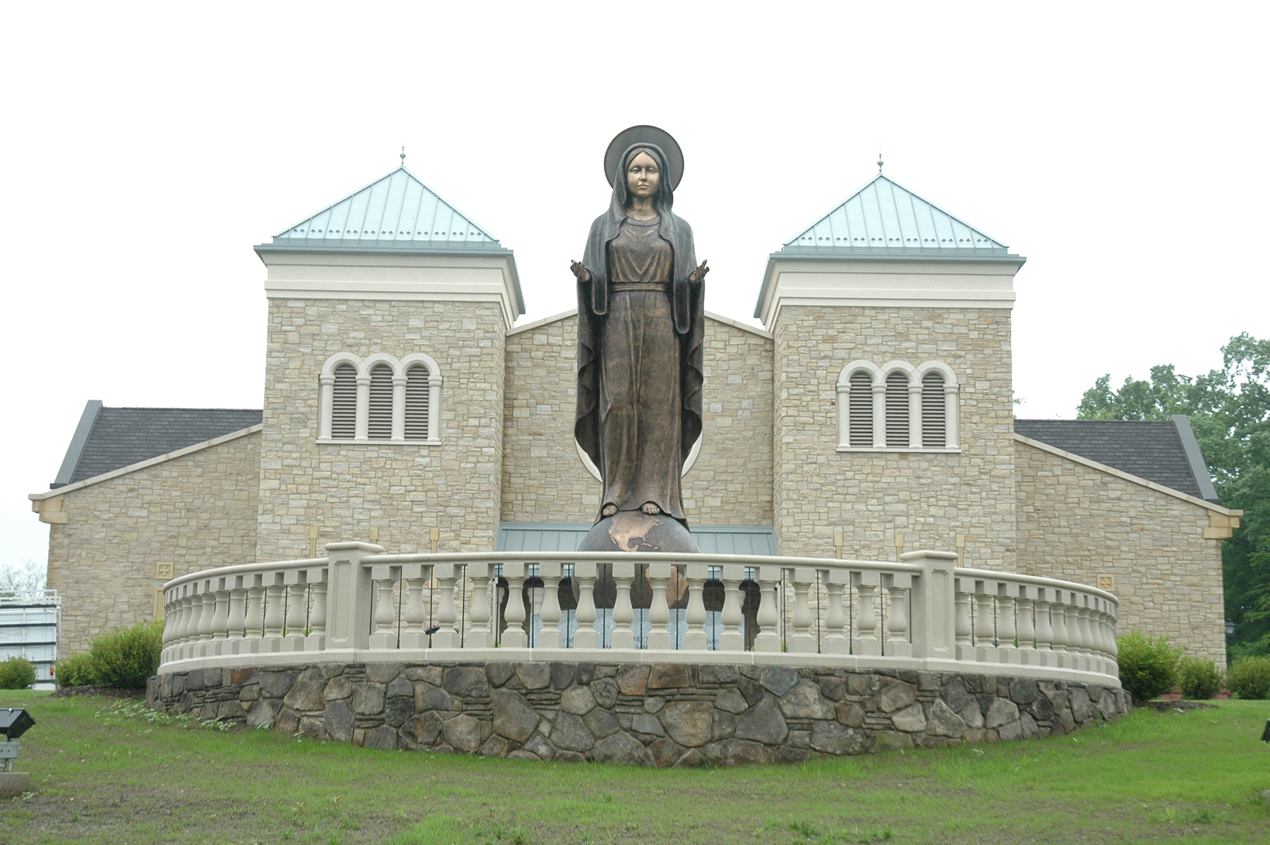 stone building with woman statue in front