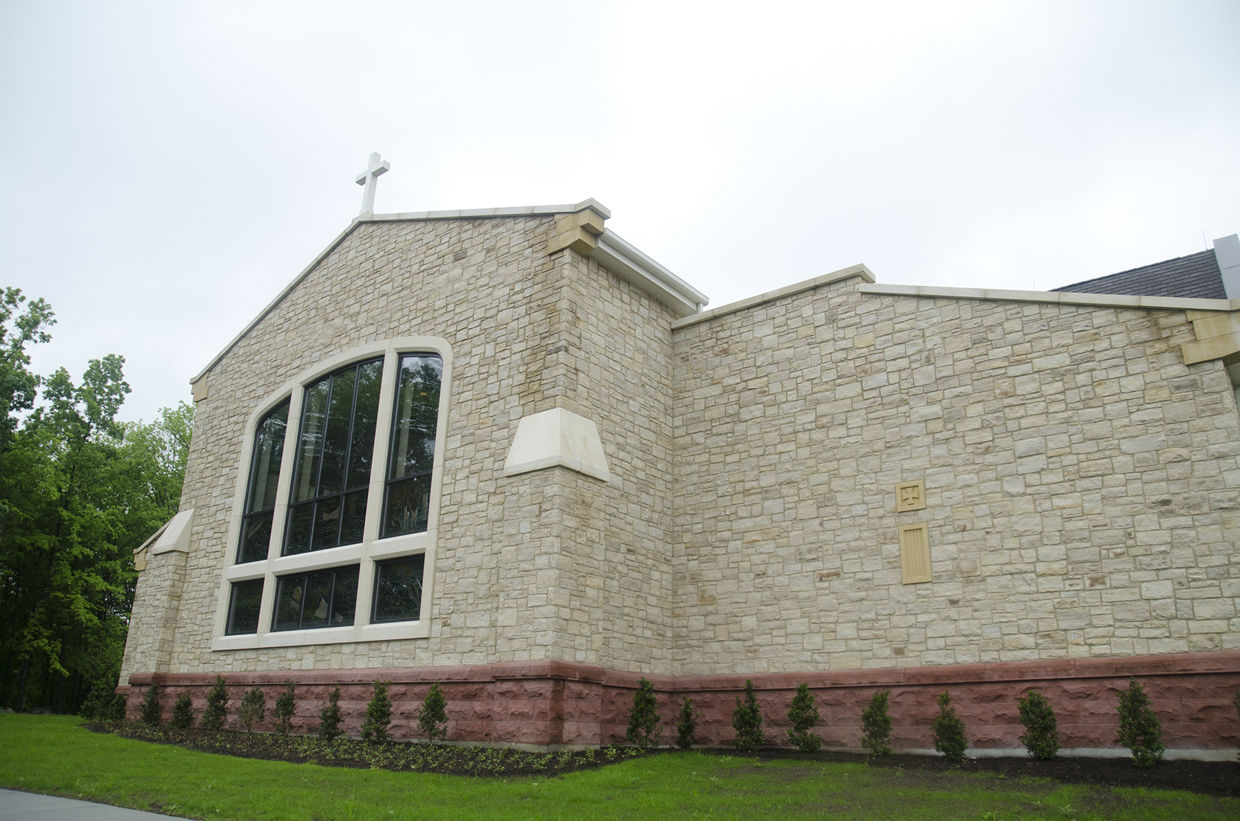 stone building with large window and cross