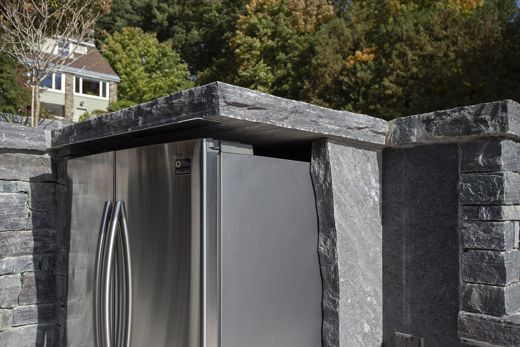 stainless steel fridge surrounded by stone