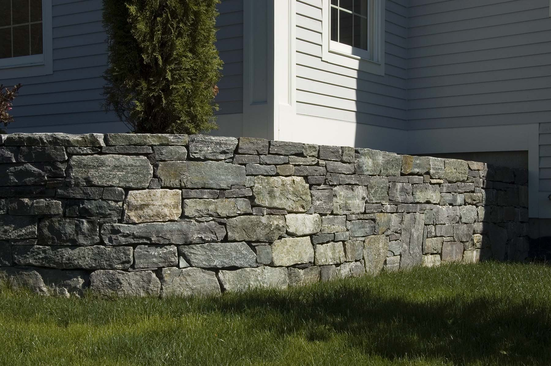 natural Adirondack stone wall by house
