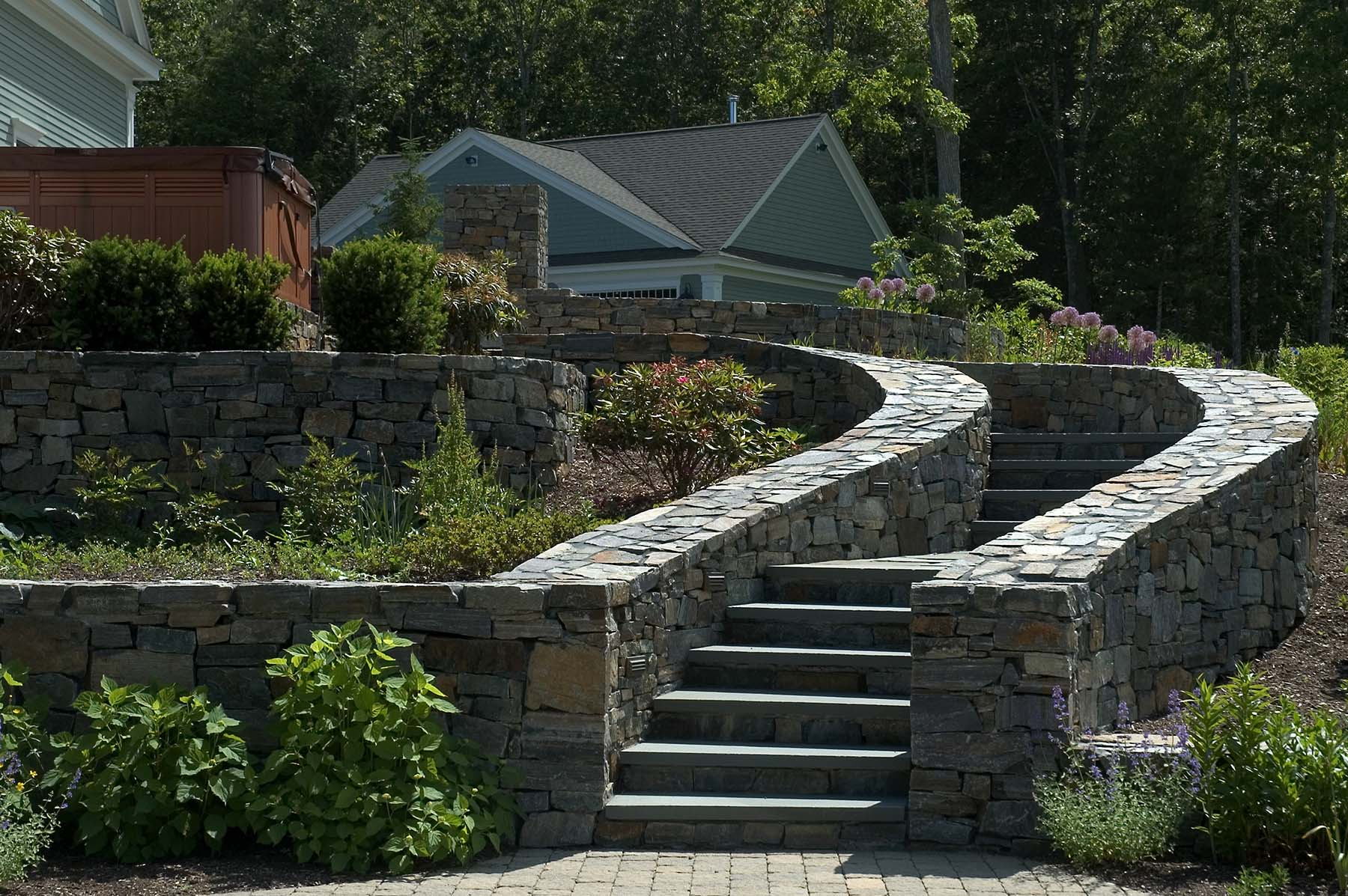 saratoga granite mosaic natural stone retaining wall and stairs outside residential home