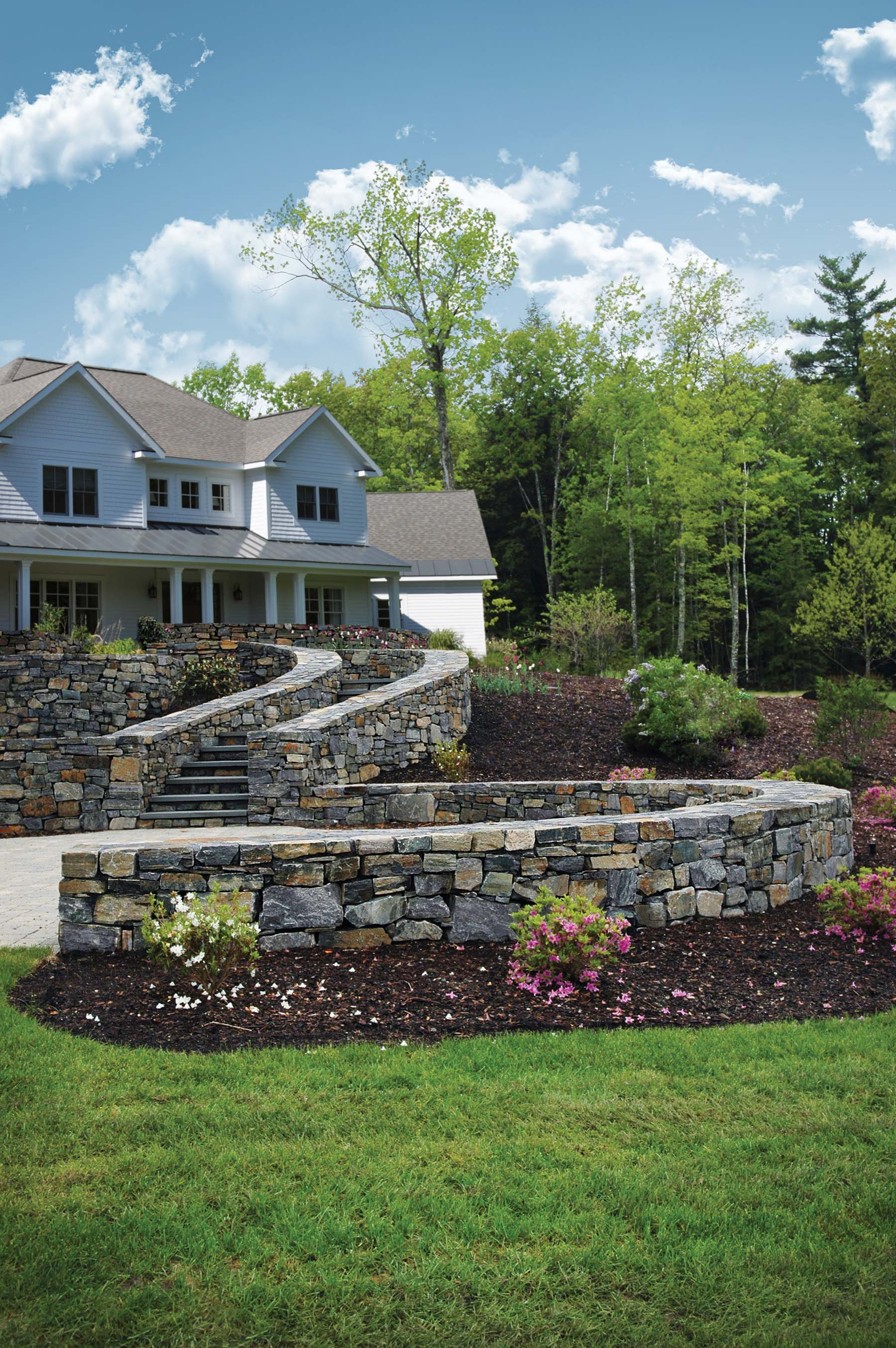 natural Adirondack stone wall surrounding house and stairs