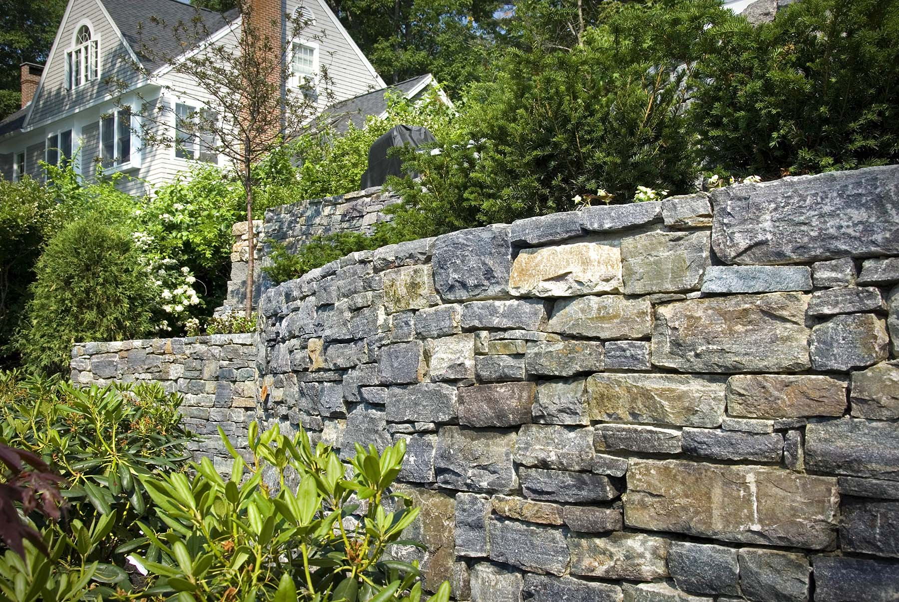 natural Adirondack stone wall by residential home