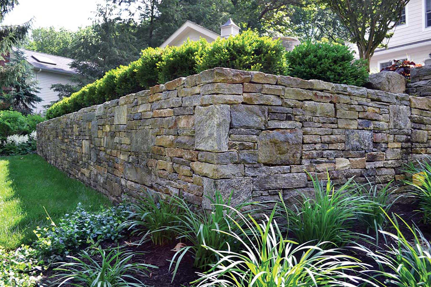 natural stone Ticonderoga granite retaining wall in residential backyard