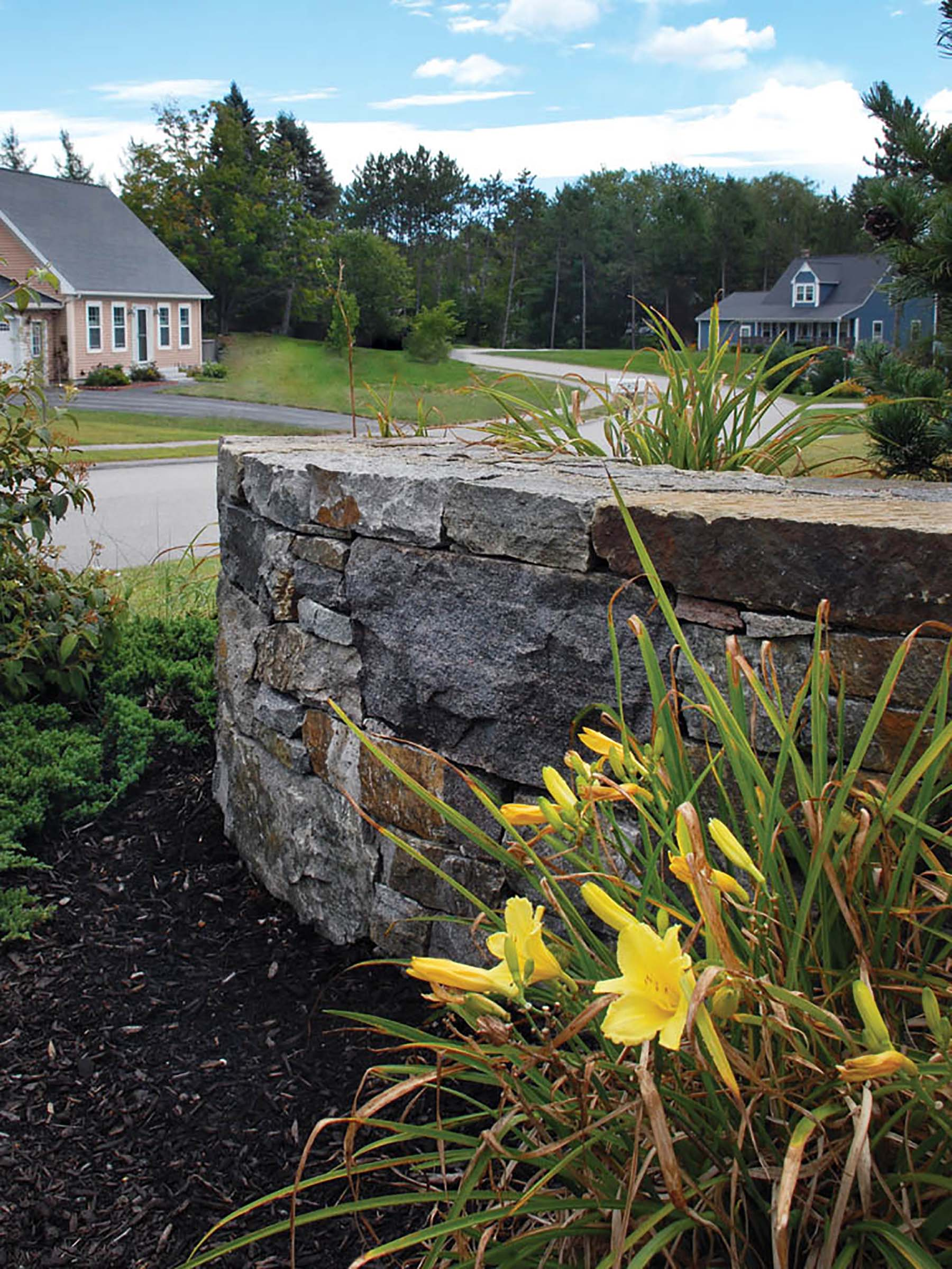 natural stone Ticonderoga wall in residential backyard