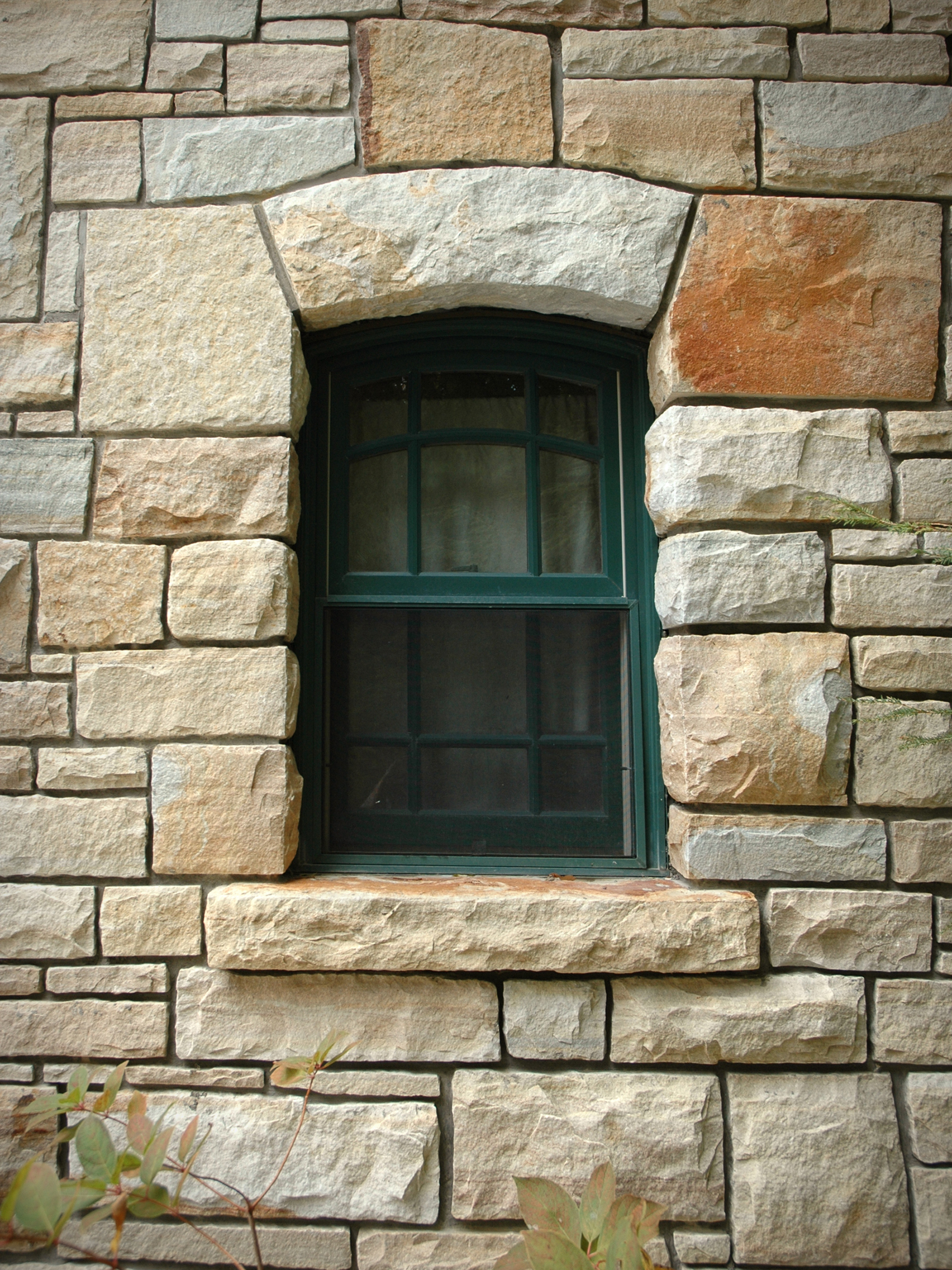 small window surrounded by stone